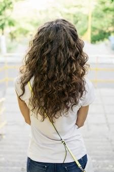 Slank meisje met krullend haar in een t-shirt en jeans op een wandeling