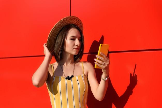 Slank meisje poseren tegen een rode muur met een telefoon