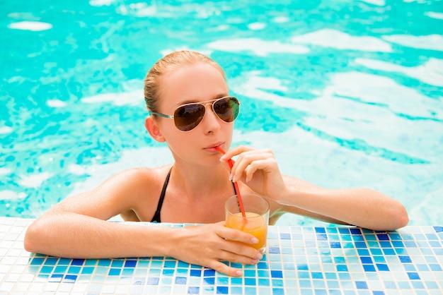 Slank meisje zwemmen in een zwembad met sap