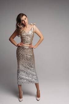 Slank model in sexy beige jurk op zoek en poseren