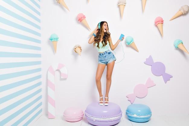 Slank opgewonden meisje in oortelefoons staande op grote paarse koekje en favoriete liedje zingen. blij dat jonge vrouw met lange bruine krullen in haar kamer danst en geniet van muziek in het weekend.