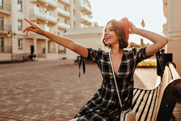 Slank romantisch meisje, zittend op een bankje met een glimlach. buiten schot van extatisch frans vrouwelijk model wijzende vinger naar iets.