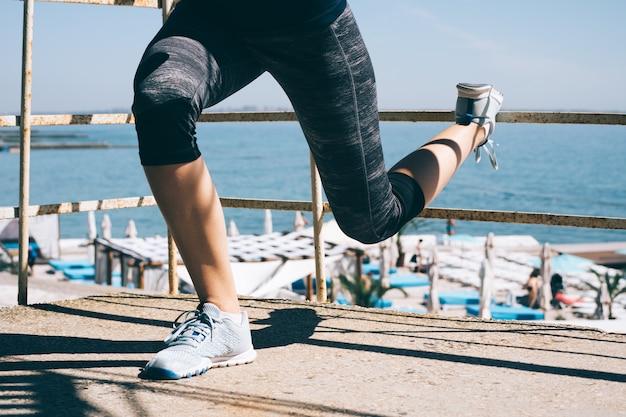 Slank sportenmeisje die sit-ups op het strand doen