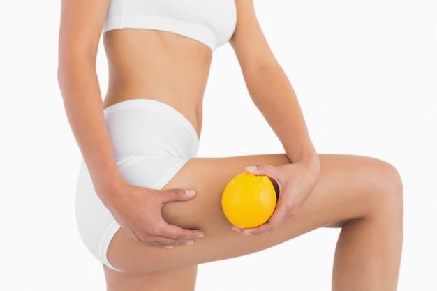 Slank vrouwelijk lichaam houdt oranje en knijpt in haar dij