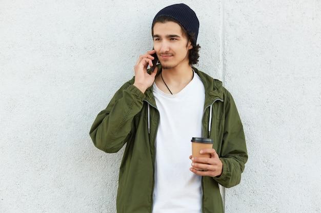 Slanke aangename jongen die opzij kijkt, zijn smartphone in de buurt van het oor houdt, geconcentreerd op het gesprek, met een wit t-shirt op