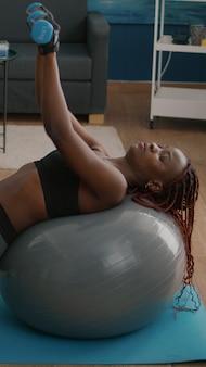 Slanke atletische vrouw met donkere huid die lichaamsspier werkt die ochtendfitnessoefeningen doet