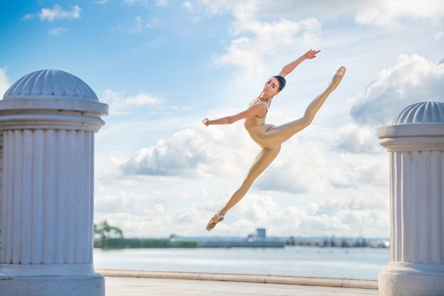 Slanke ballerina in pointe-schoenen en bruidskostuum springt tegen de achtergrond van de zee