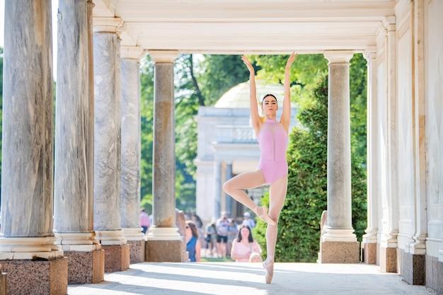 Slanke ballerina in pointe-schoenen en het dragen van een silhouetkostuum dat danst tegen de achtergrond van antieke architectuur in het park