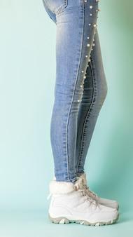 Slanke benen van een meisje in een strakke spijkerbroek en warme gympen