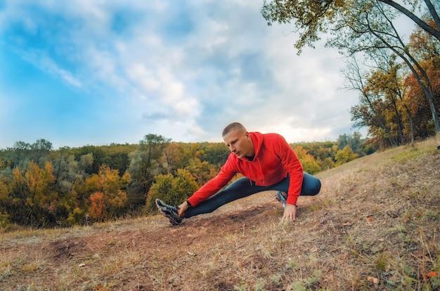 Slanke blanke jogger man in rood jasje en zwarte sportlegging voert warming-up uit voor het joggen