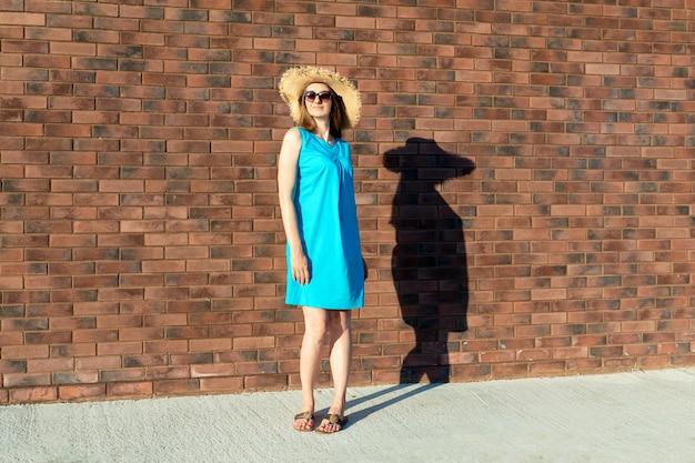 Slanke blanke vrouw in blauwe jurk en strooien hoed met vette schaduw op de muur.