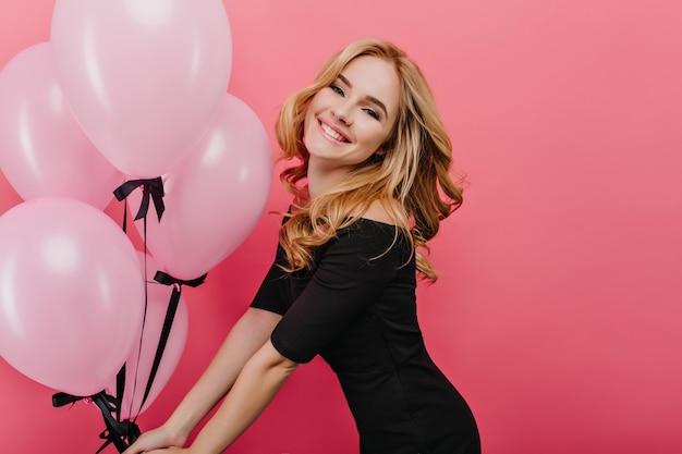 Slanke blanke vrouw met krullend kapsel viert haar verjaardag en gelukkig lachen. binnenfoto van vrolijk kaukasisch meisje dat op roze muur in vakantie danst.