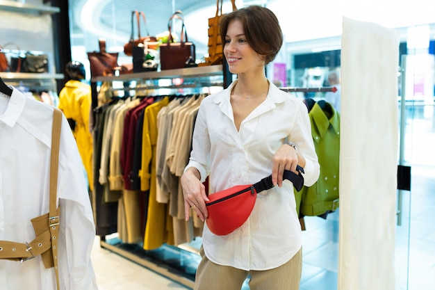 Slanke blanke vrouw met rode heuptas op haar taille.