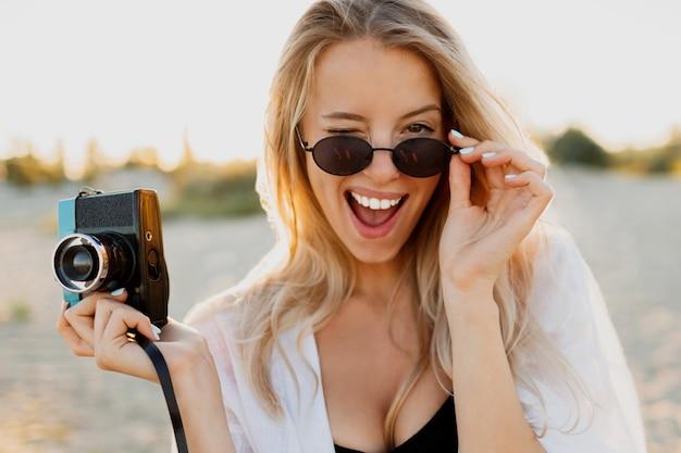 Slanke blonde gelukkige vrouw die retro camera houdt en pret op warm zonnig strand heeft. zomervakantie en reizen concept. natuurlijke schoonheid, vakantie in azië. trendy zonnebril, witte outfit.
