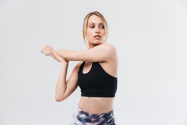 Slanke blonde vrouw gekleed in sportkleding die aan het trainen is en haar lichaam strekt tijdens aerobics geïsoleerd over een witte muur