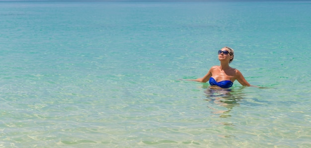 Slanke blondevrouw die op tropisch strand zwemmen