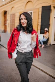 Slanke brunette dame in grijze broek poseren met zachtjes glimlach op straat