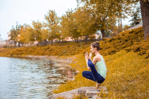 Slanke brunette meisje gaat sporten en voert yoga houdingen in de herfst in de natuur uit