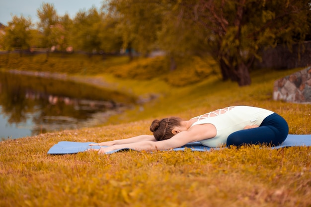 Slanke brunette meisje gaat sporten en voert yoga houdingen uit in de herfst aan het meer