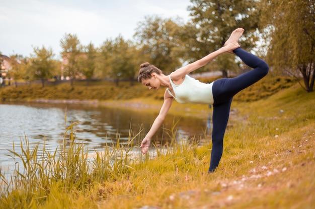 Slanke brunette meisje gaat sporten en voert yoga houdingen uit in de herfst bij het meer