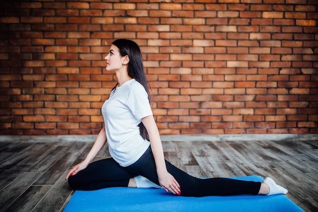 Slanke brunette vrouw beoefent yoga in studio met witte achtergrondverlichting. gezond leven.