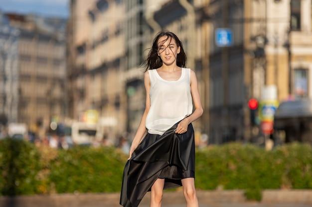 Slanke brunette vrouw in rok loopt overdag buiten