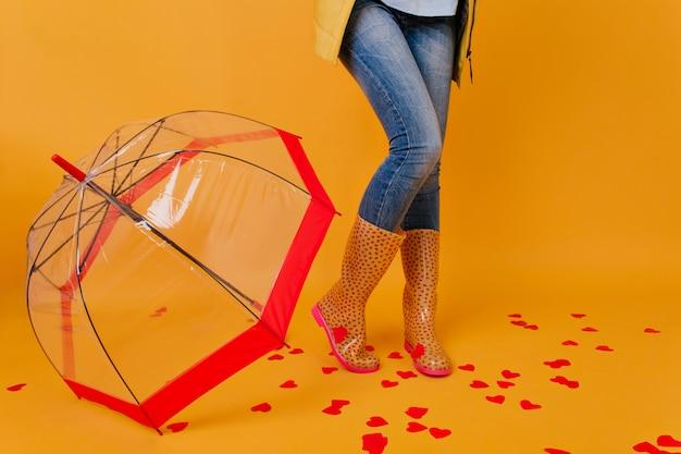 Slanke dame in blauwe denim broek staande op de vloerbedekking met papieren hartjes. vrouwelijk model in rubberen schoenen poseren naast rode parasol.