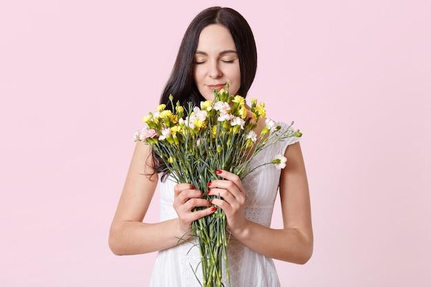 Slanke donkerbruine vrouw die geel roze boeket houdt, haar ogen sluit, geur van lentebloemen voelt, die witte kleding draagt.