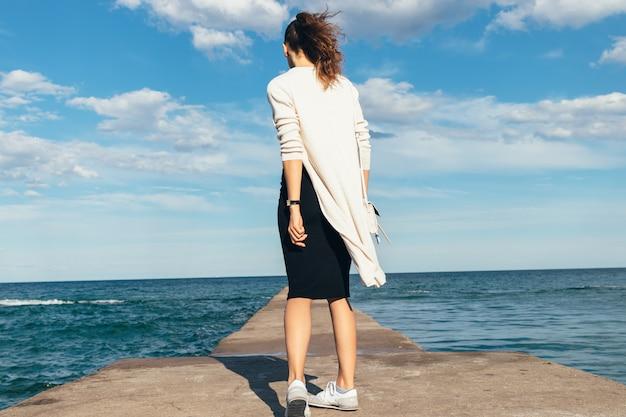Slanke donkerbruine vrouw in een rok, cardigan en tennisschoenen die op het strand in de zomer lopen