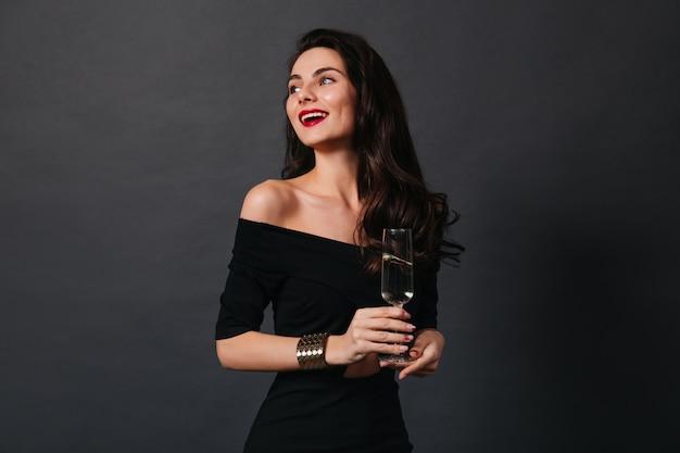 Slanke donkerharige dame in kleine zwarte jurk en stijlvolle gouden armband glimlacht terwijl ze glas wijn vasthoudt op geïsoleerde achtergrond.