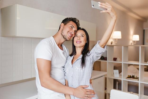 Slanke donkerharige vrouw selfie met echtgenoot maken voor het ontbijt