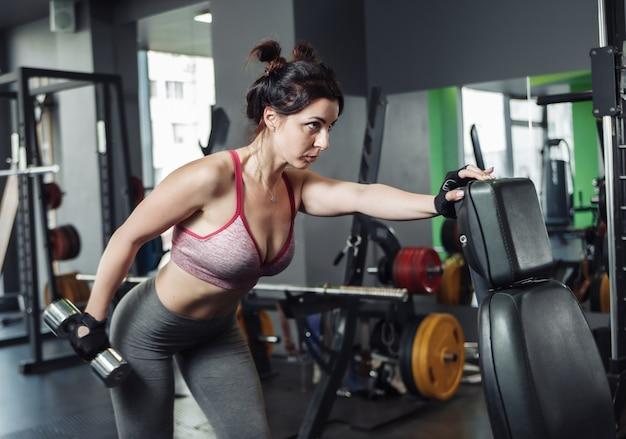 Slanke fit vrouw oefenen verlenging van een arm met een halter in een helling.