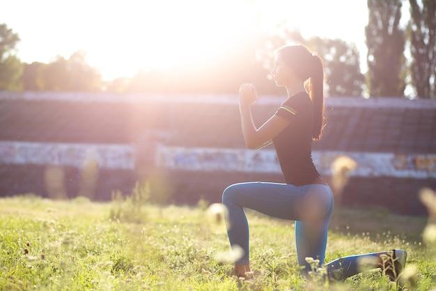 Slanke fitness vrouw doet lunges in het stadion met schittering van de zon. ruimte voor tekst