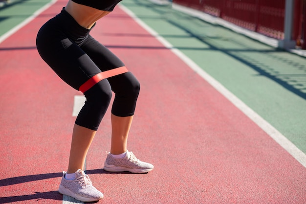 Slanke fitnessvrouw die een vrouw doet die squats doet met een rubberen weerstandsband op een brug. ruimte voor tekst