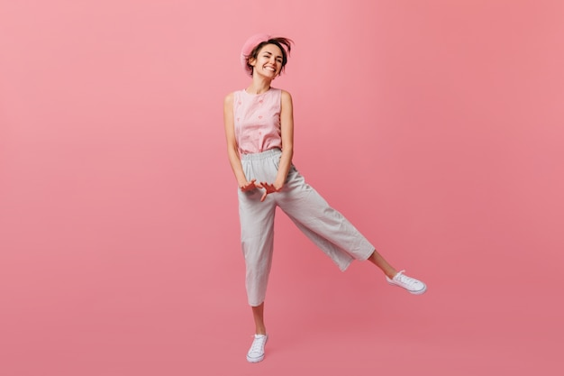 Slanke franse vrouw grappig dansen op roze muur