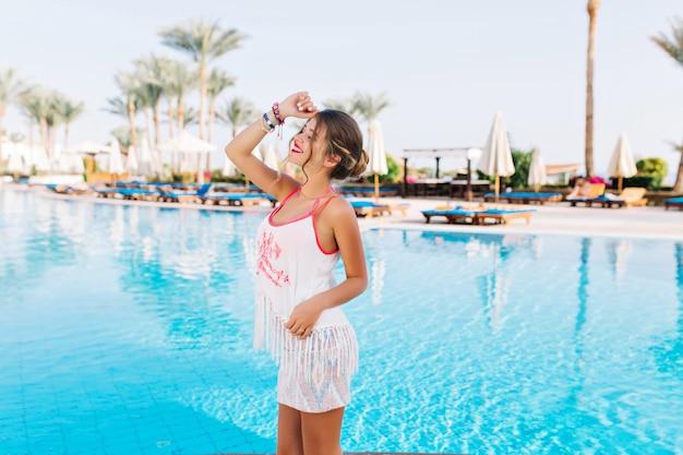 Slanke, gebruinde jongedame in tanktop met franjes en rok poseren, haar gezicht bedekt tegen zonlicht