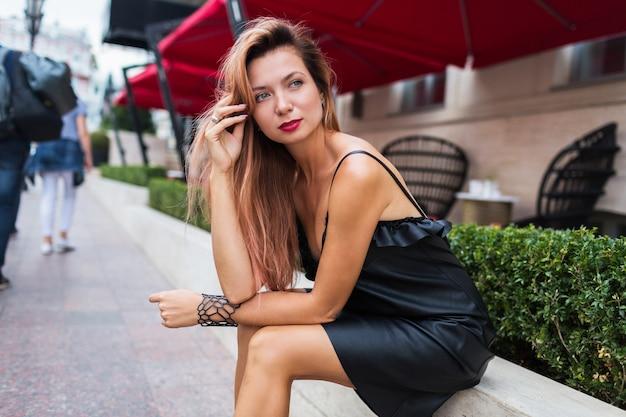 Slanke gelooide vrouw in elegante zwarte jurk en hakken met heldere blonde haren poseren in oude europese stad in de buurt van luxe restaurant.