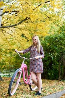 Slanke gelukkige blonde modieuze aantrekkelijke vrouw met roze damefiets die zich alleen onder lange boom op mooi groen en gouden zonnig de herfstgebladerte bevinden