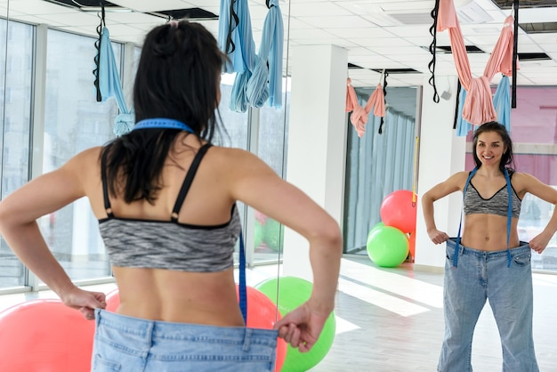 Slanke gelukkige vrouw in oversized jeans in de fitnessruimte. vrouwelijke levensstijl. fit en dieet