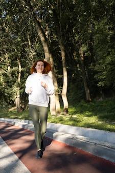 Slanke gembervrouw in sportkleren die in park op ochtend gezonde fitness levensstijl lopen