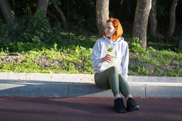 Slanke gembervrouwenloper in sportkleding die in park drinkwater gezonde fitness levensstijl zit