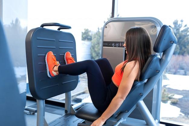 Slanke glimlachende vrouw gebruikend een beenpersmachine en plaatsend haar benen op het platform