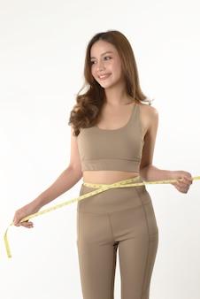 Slanke jonge aziatische vrouw die haar lichaam meet