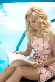 Slanke jonge blonde leest restaurantmenu bij het zwembad in luxehotel