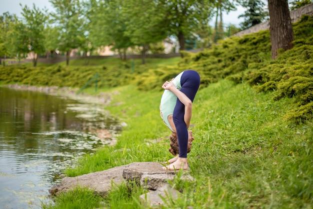 Slanke jonge brunette meisje yogi doet moeilijke yoga-oefeningen op het groene gras op de scène van water