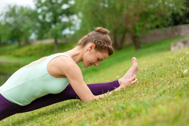 Slanke jonge brunette yogi voert complexe yoga-oefening op groen gras in de zomer uit