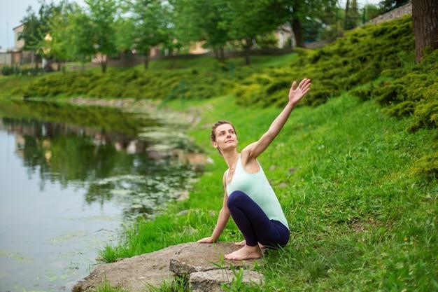 Slanke jonge brunette yogi voert geen ingewikkelde yoga-oefeningen op het groene gras in de zomer uit tegen de achtergrond van de natuur