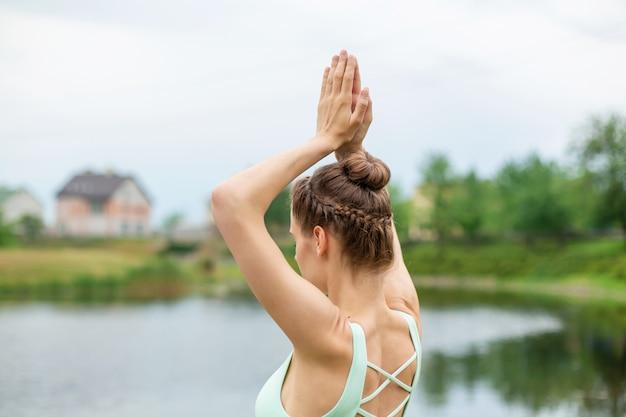 Slanke jonge brunette yogi voert geen ingewikkelde yoga-oefeningen op het groene gras in de zomer uit tegen de natuur