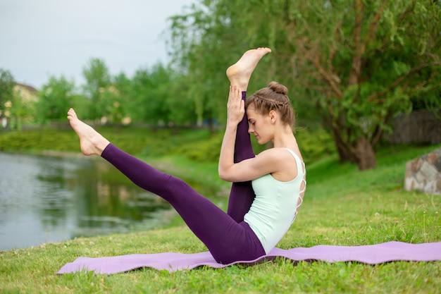 Slanke jonge brunette yogi voert geen ingewikkelde yoga-oefeningen op het groene gras in de zomer uit tegen de scène van de natuur