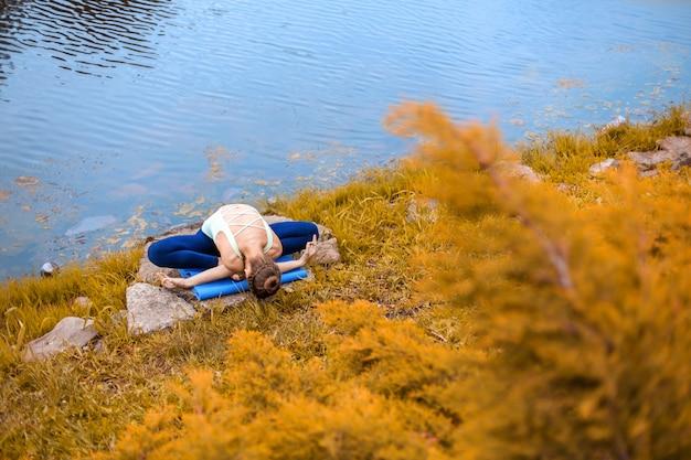 Slanke jonge brunette yogi voert uitdagende yogaoefeningen op het groene gras in de herfst uit tegen de achtergrond van de natuur